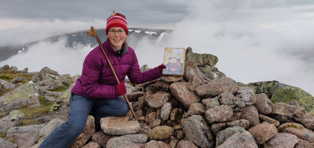 Merryn Glover planting tin containing novel Of Stone and Sky on top of Angel's Peak in the Cairngorms