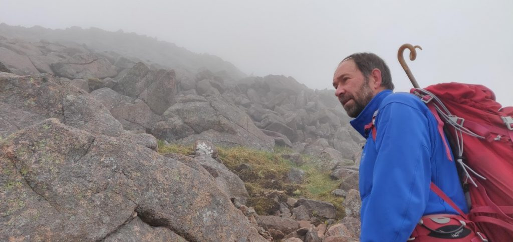 John Lyall, mountain guide, with backpack in the Cairngorms in the mist