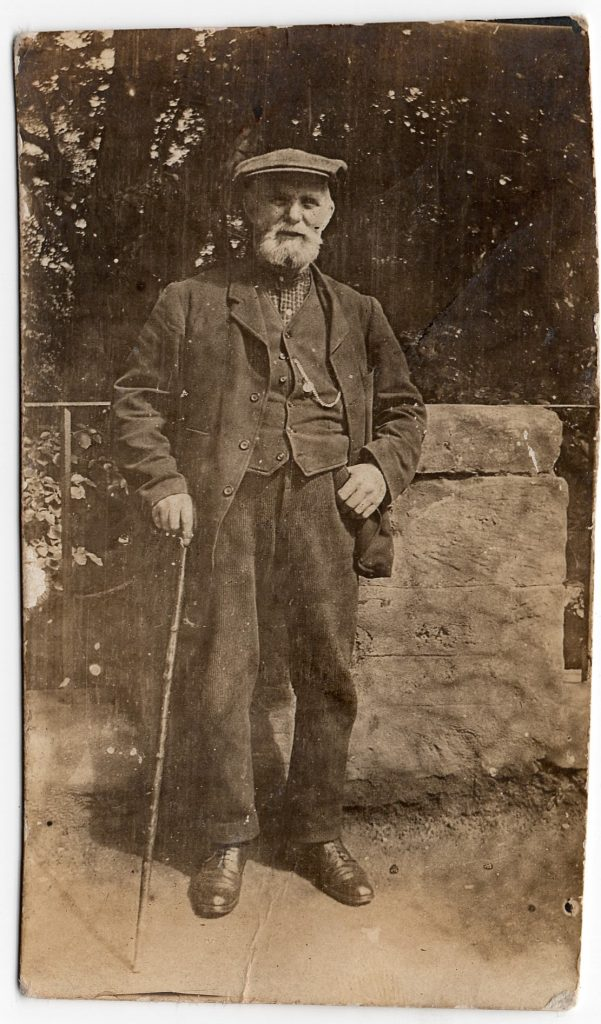 Sepia photograph of an old man with a walking stick, early 20th Century