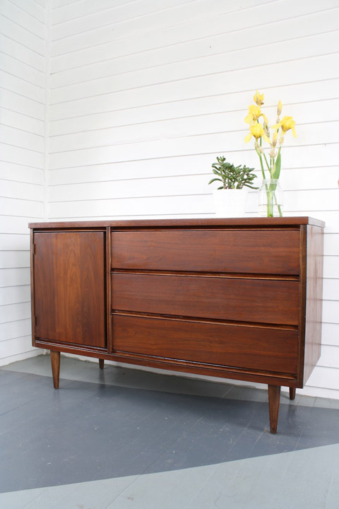 A refinished wooden sideboard left with a natural stain – not painted! Learn how to refinish this sideboard.