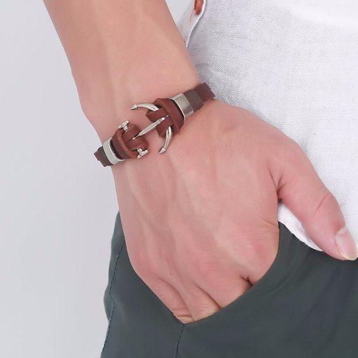 bracelet ancre en cuir marron porte par un homme main gauche dans la poche