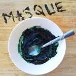Mascarilla de espirulina: receta elaborada en un bol blanco, los ingredientes mezclados con una cuchara.  Máscara escrita en el soporte de madera, con la receta de la espirulina.