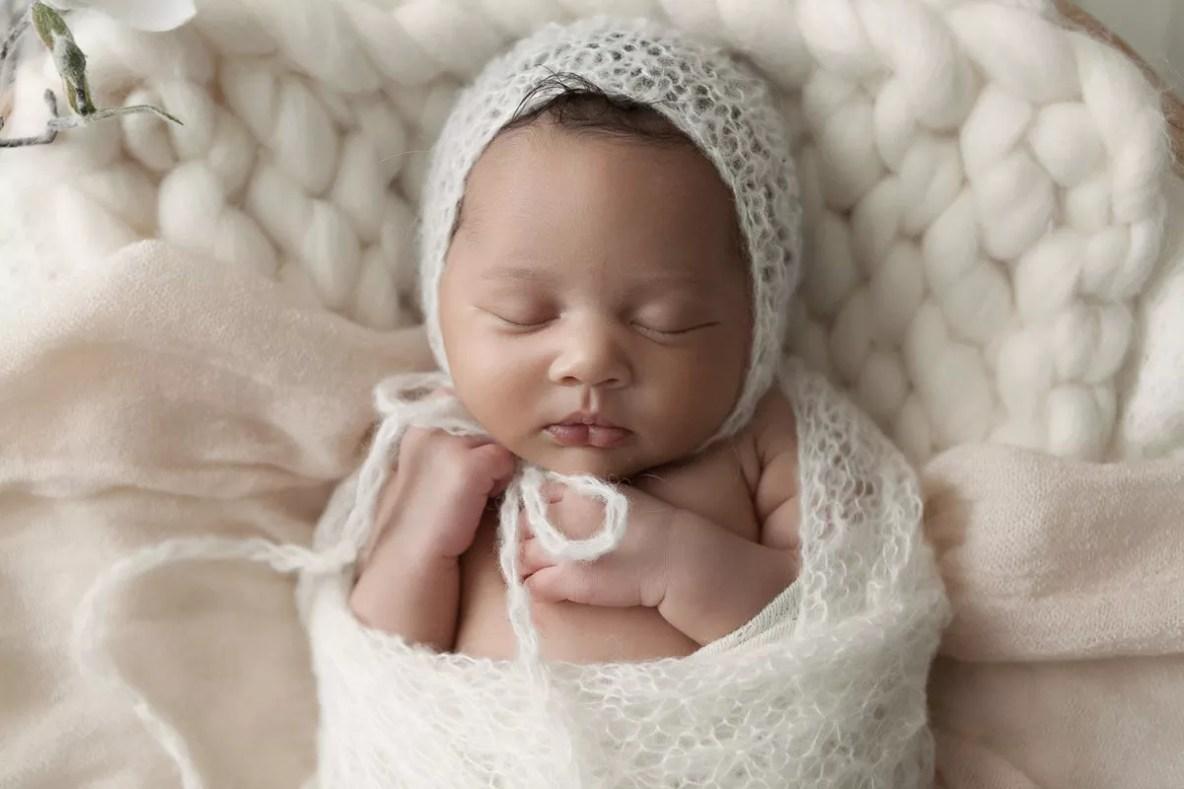 nouveau-né métisse endormi emmailloté