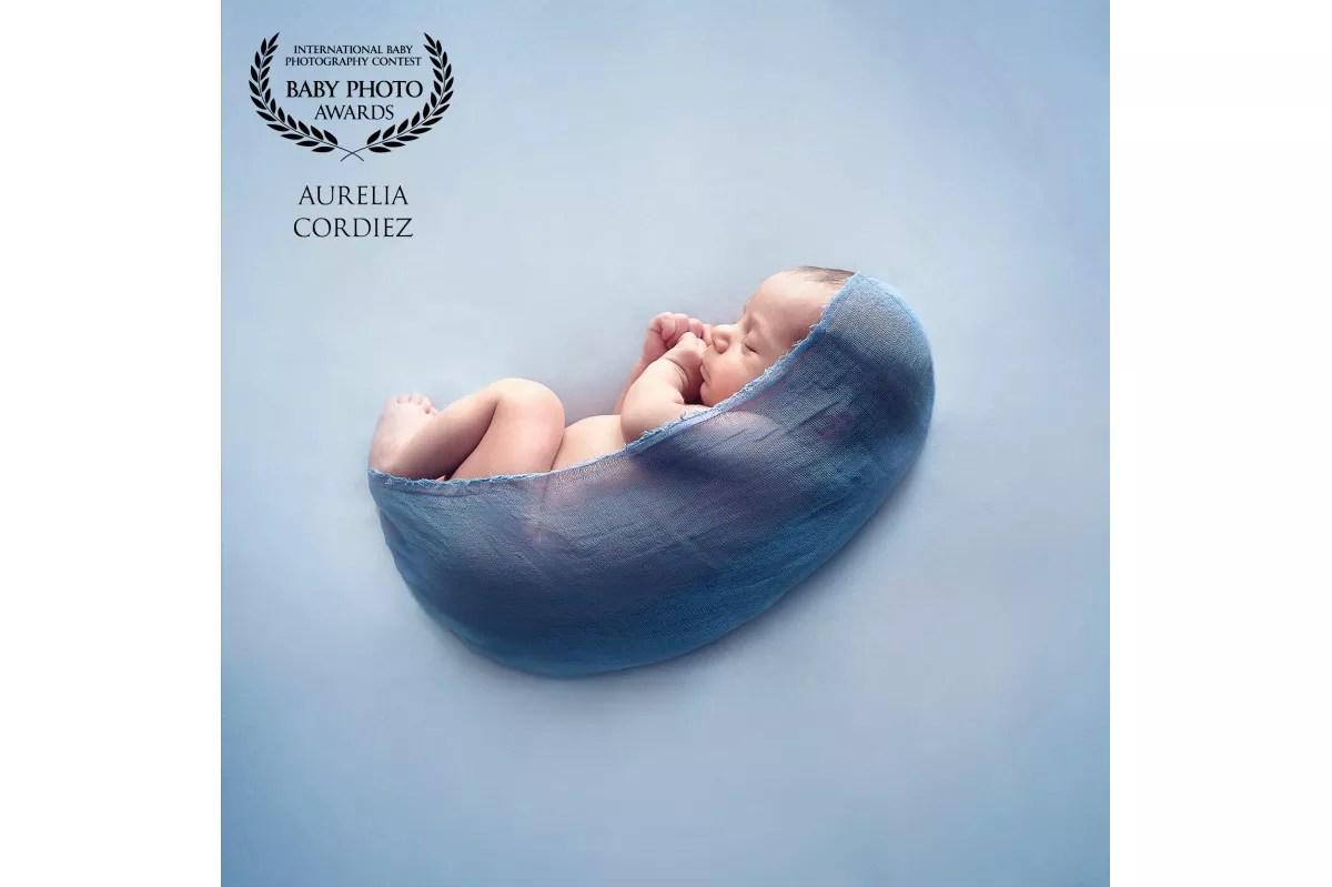 photo nouveau-né minimaliste dans cocon de tissu bleu photo gagnante AFNS AWARD