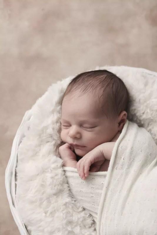 portrait minimaliste nouveau-né endormi dans panier avec fourrure crème