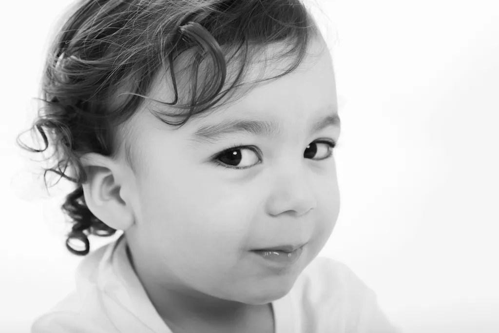 portrait noir et blanc petit garçon aux cheveux bouclés et air coquin