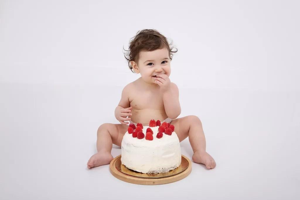 bébé qui goûte son gâteau d'anniversaire avec des framboises