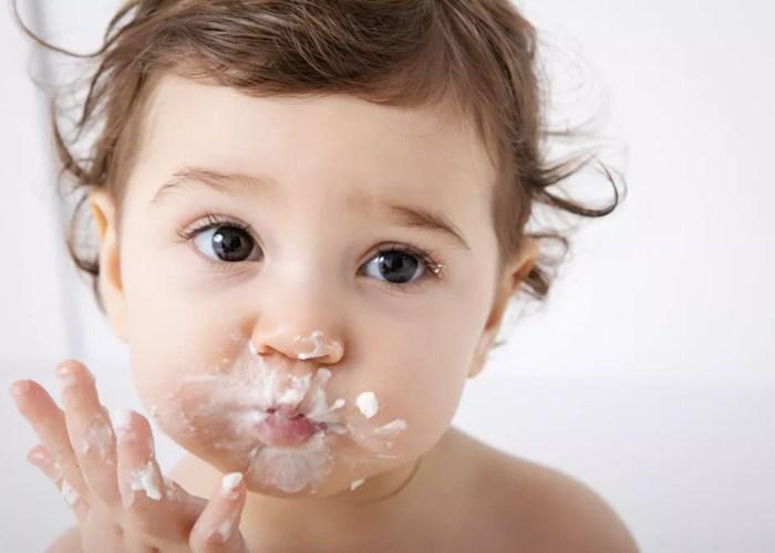 bébé avec la bouche peine de crème pendant séance photo smash the cake