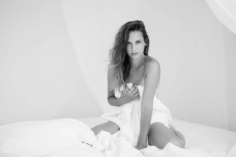shooting photo boudoir proche paris dans lit à baldaquin ambiance claire et épurée