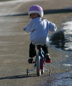 girl on bicycle with training wheels