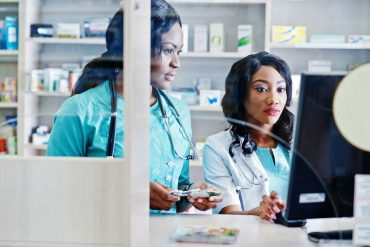 Two african american pharmacist working in drugstore at hospital pharmacy. Health Care Costs
