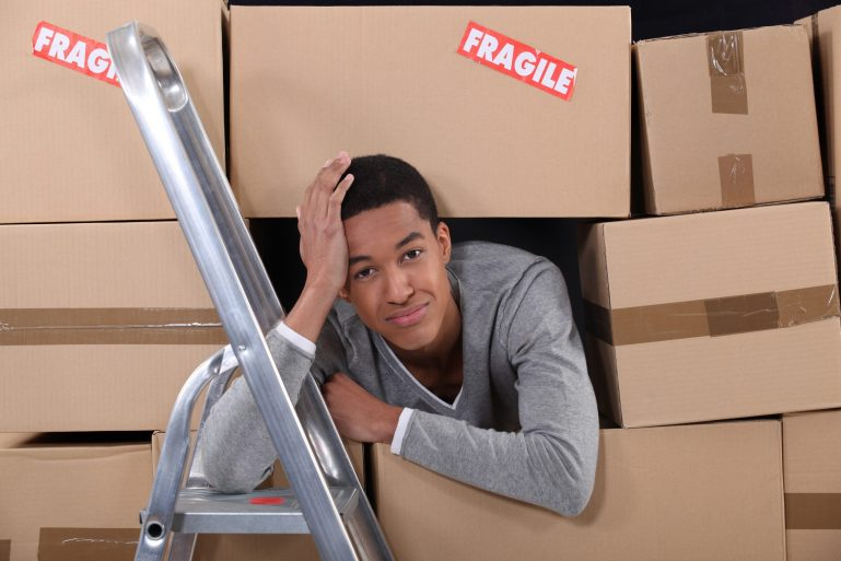 young man surrounded by boxes moving into a new apartment
