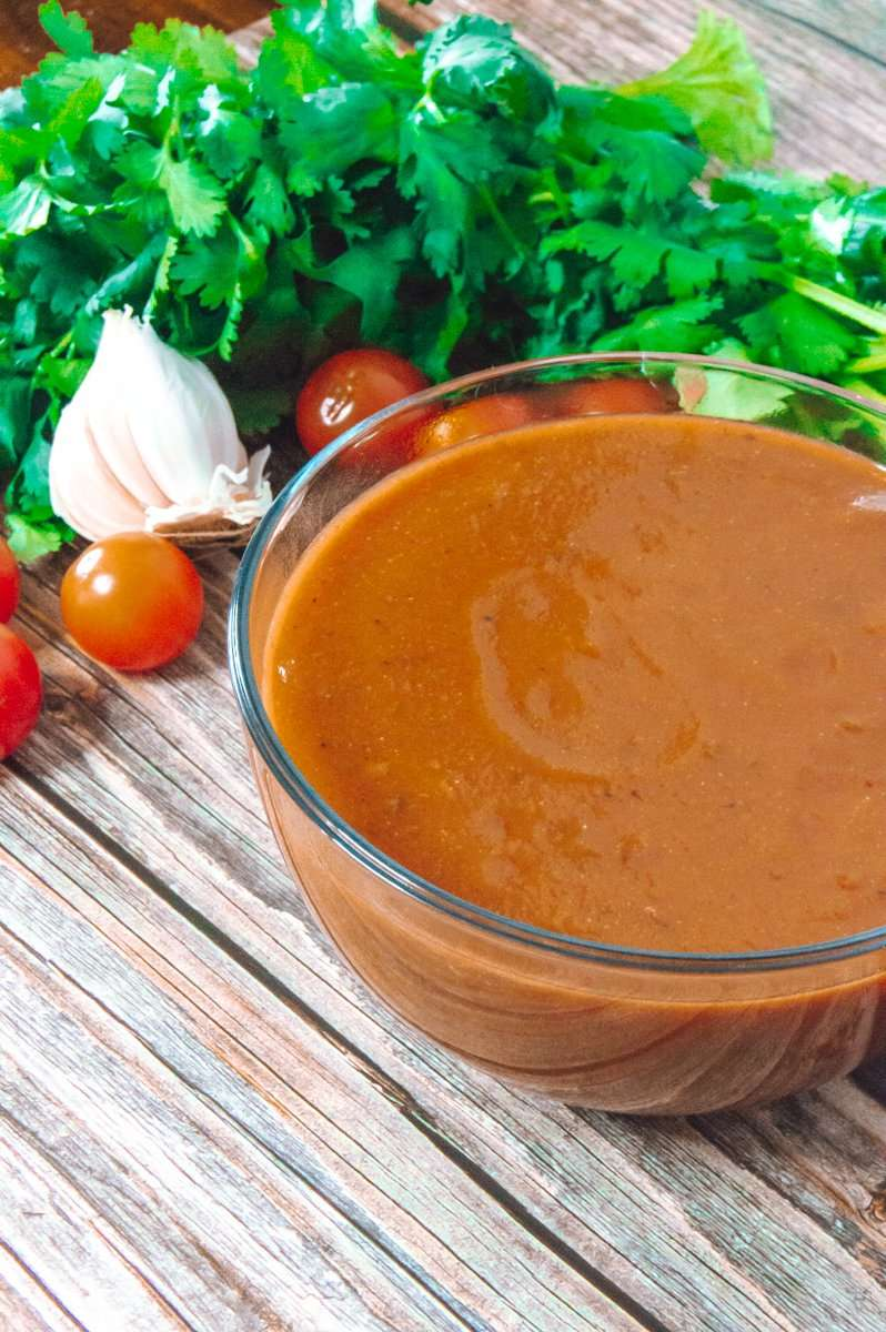 Chipotle Enchilada Sauce up close with ingredients in the background