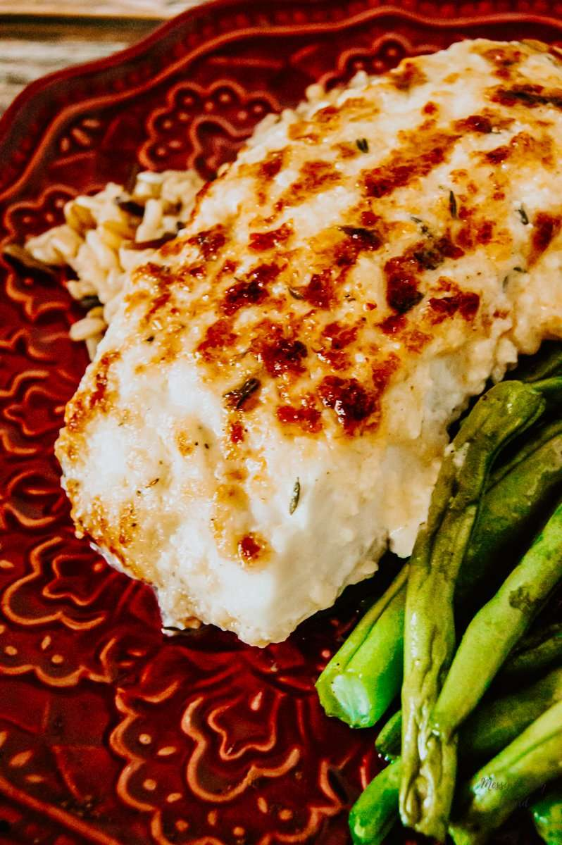 Up close to a fillet of Lemon-Herb Baked Halibut with wild rice and fresh green beans