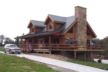 This log cabin has some upgrades from your typical cottage, including a stone chimney and a gorgeous roof from Metal Roof Outlet, Ontario.