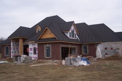 This Ontario contractor is building a home with a lot of classic features - red bricks, black shake - but the quality is evident in the stonework around the windows and doors, as well as the upgrade to steel shake from Metal Roof Outlet.