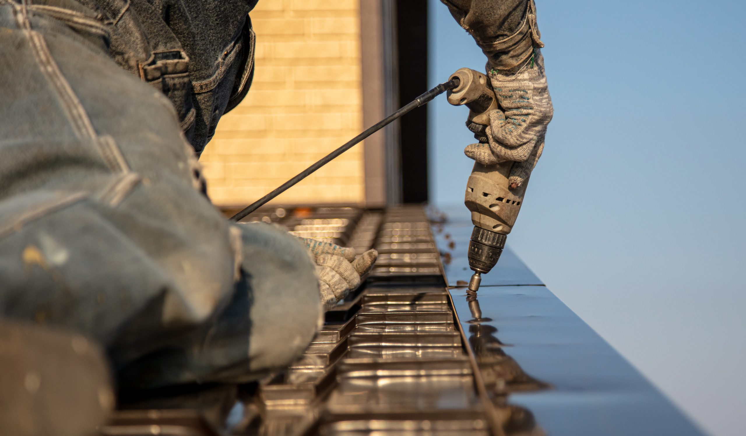 metal roof installer drilling shiny new metal sheets onto roof