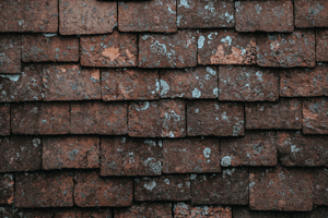 Close-up of an crumbling and stained brown asphalt roof showing signs of wear and decay
