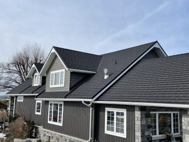 Grey brick and siding house in Blenheim, Ontario with new CF Shingle metal roof tile in the colour Charcoal