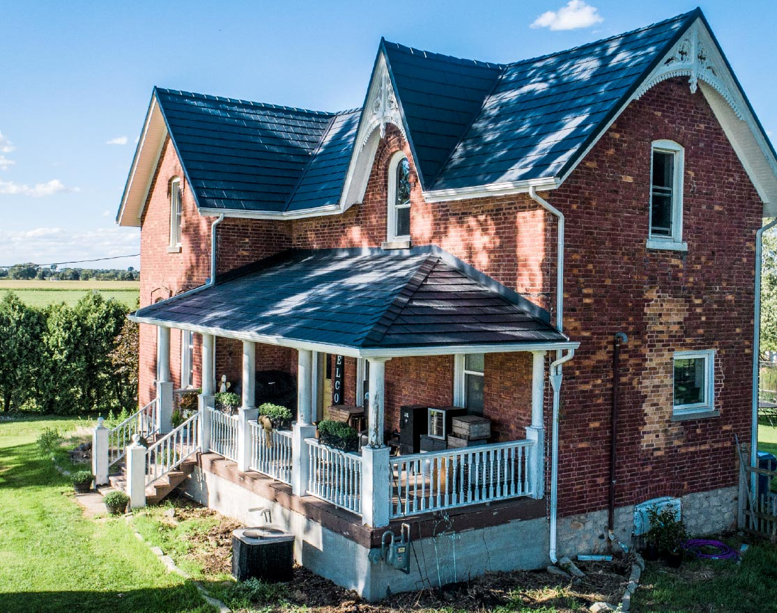 Deep Grey Metal Tile Resembles Slate Roof on red brick 1900s farmhouse with white fenced porch in the middle of a green field