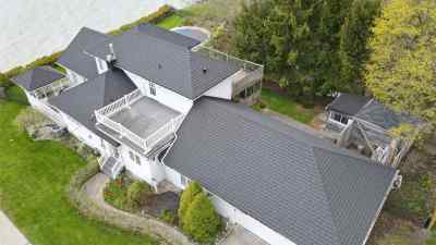 Aerial view of a charcoal metal roof on a white cottage with a lake and trees in the background. Cottage located in Port Stanley, Ontario with Tilcor CF Shingle metal roof by metalroofoutlet.com