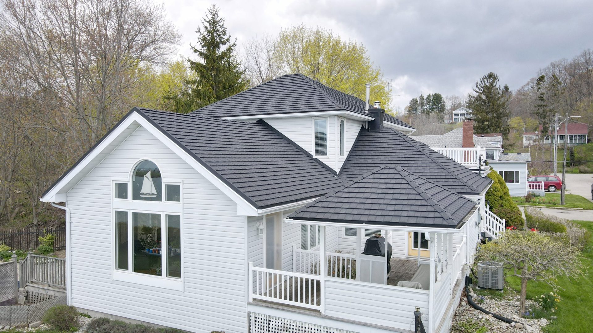 White house with grey metal roof from Metal Roof Outlet with trees and homes in the background