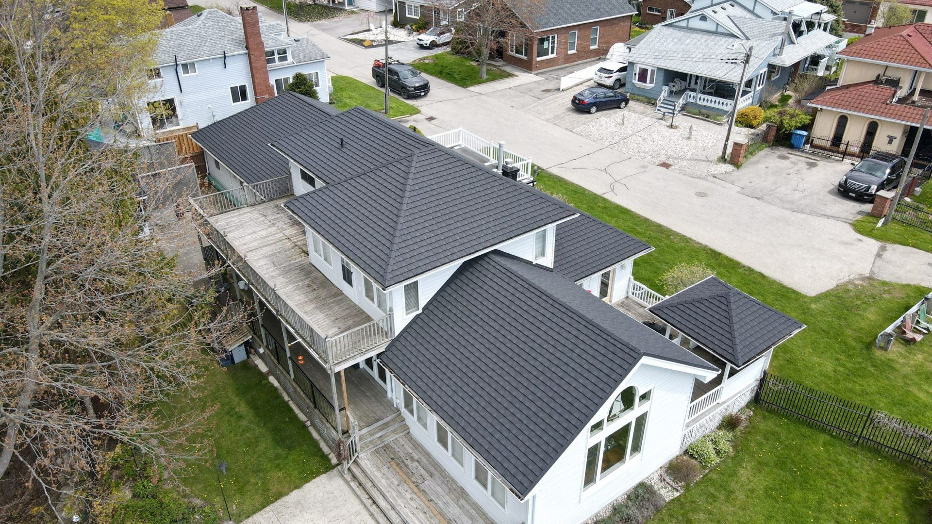 Aerial view of attached garage on a white cottage with a green lawn, trees and a blue cloudy sky in the background. Cottage located in Port Stanley, Ontario with Tilcor CF Shingle metal roof by metalroofoutlet.com