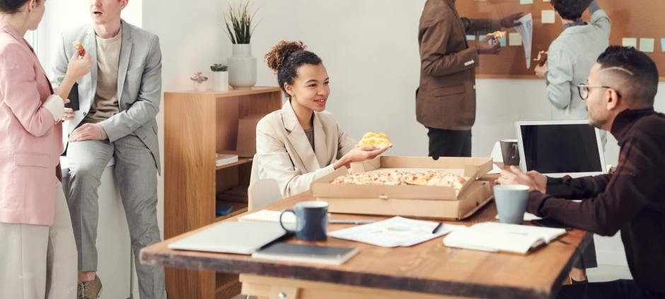 image of people eating pizza at work for blog by Metis HR on working time regulations