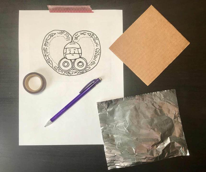 crafting materials to make your own ornament: a drawing on a pieces of paper, tape, cardboard, a pen, and a small rectangle of tin foil.