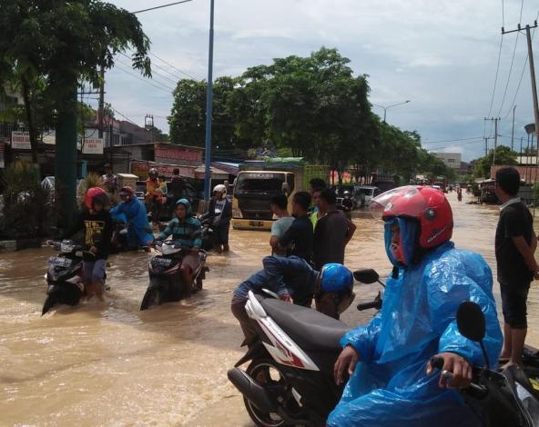 Sejumlah pengendara roda dua terpaksa mendorong motornya akibat banjir di Jalan DI Panjaitan.