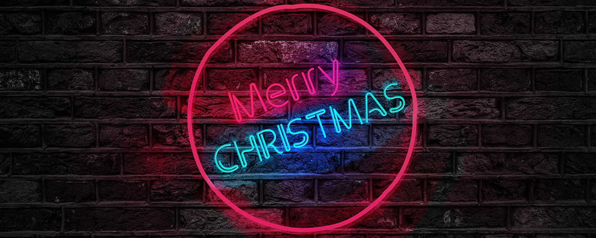 Texto en neón Merry Christmas sobre pared de ladrino