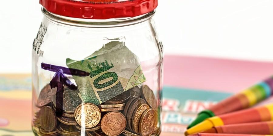 doorzichtige spaarpot met muntjes en briefgeld. rechts van de spaarpot liggen er krijtjes
