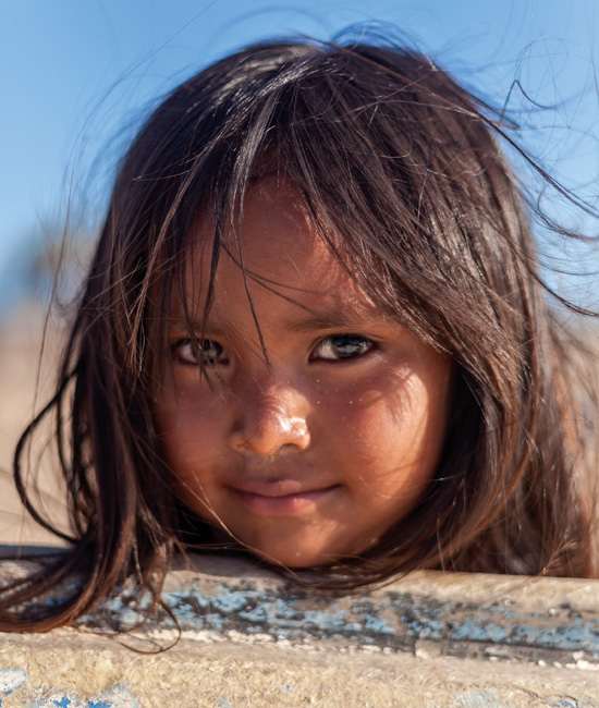 David Paniagua / A Seri girl rests her copper face on a boat stranded on the beach.