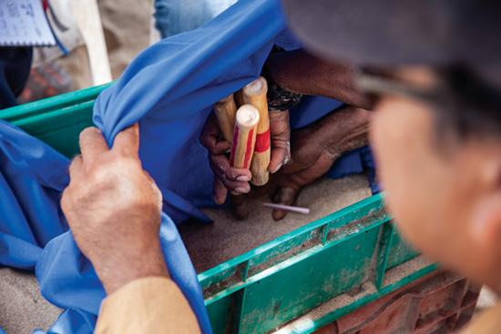 David Paniagua / Men play with reeds on a sandbox.