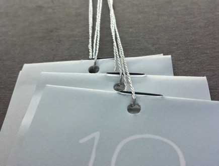 Stitched booklets on thin silver gray stock strung with 3-ply silver lamé.