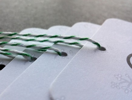 Tags with rounded corners and foliage graphic strung with green bakery twine.