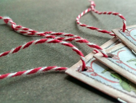 Stitched booklets strung with heavyweight variegated red-white cotton string.