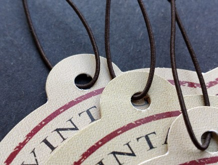 Tan die-cut tags with a maroon border strung with brown non-fray elastic.