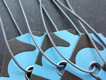 Brown tags with blue copy strung with gray non-fray elastic.