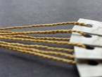 Narrow tags in neutral hue strung with lightweight 1200 gold Pearlray.