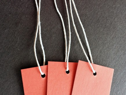 Red-orange tags strung with polished cord.