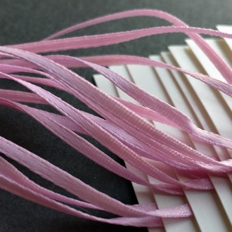 """White tags strung with light pink 1/16"""" double-faced satin ribbon."""