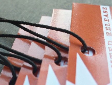 Red ochre tags strung with standard elastic in black.