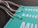 Teal museum tags with white copy strung with standard white rayon string.