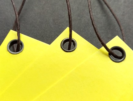 Tags of yellow cover stock reinforced with our black eyelets and strung with our black waxed cord.