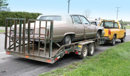 Cadillac on a flatbed with grill and towed by yellow truck