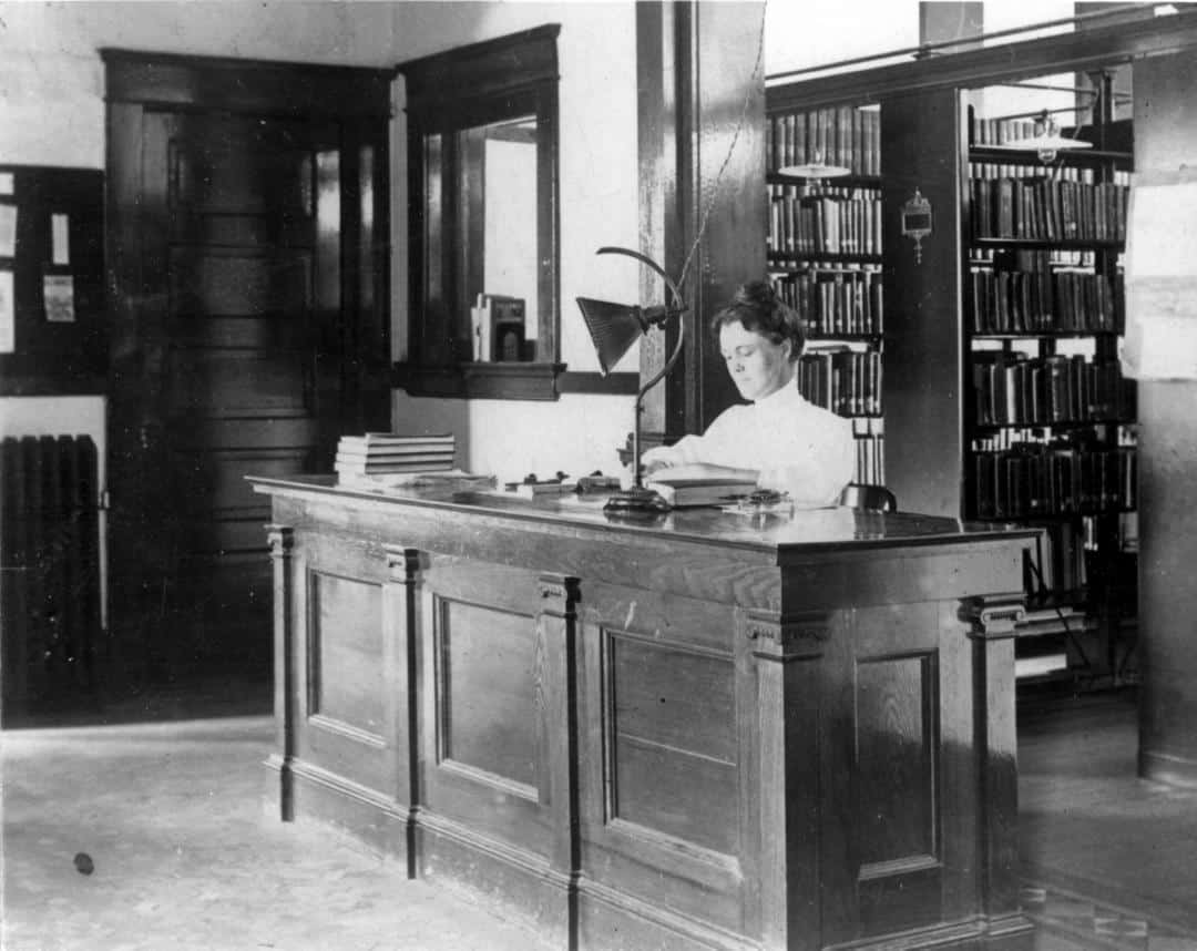Mary Cornelia Lee is sitting behind a wooden desk stamping a book.