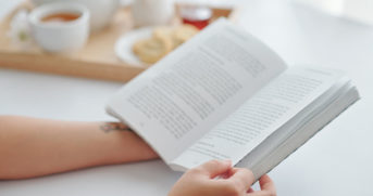 Close-up image of young woman having breakfast and reading book at home in the morning