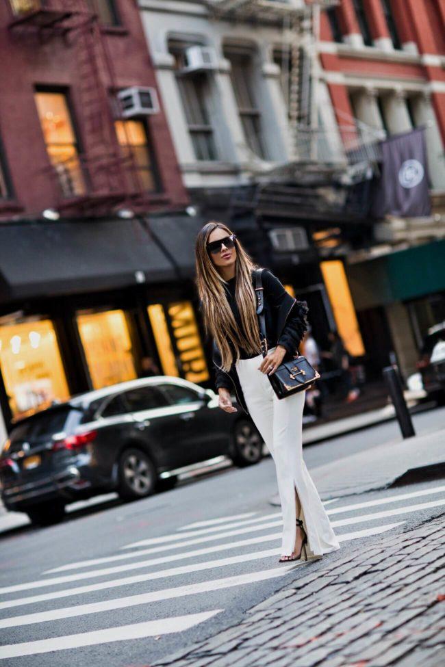 fashion blogger mia mia mine wearing white pants and a black fringe zara jacket at nyfw