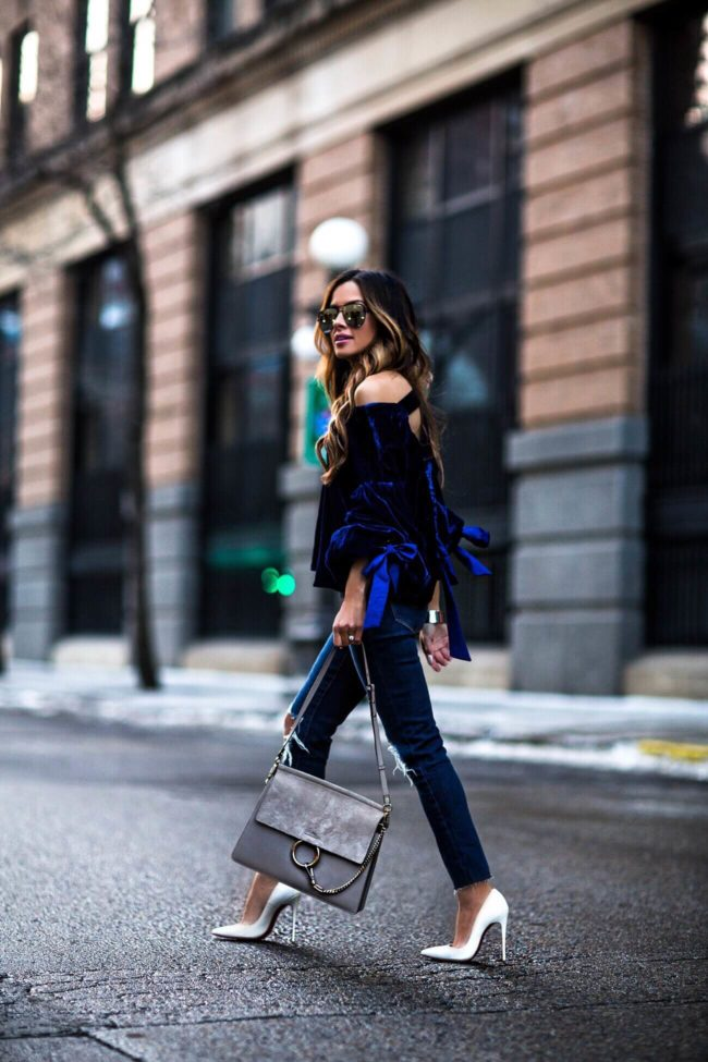 fashion blogger mia mia mine wearing a blue velvet top and chloe faye bag